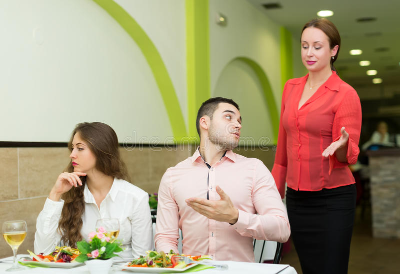 Dissatisfied visitors in restaurant. Angry men talking with courteous women manager in restaurant stock image