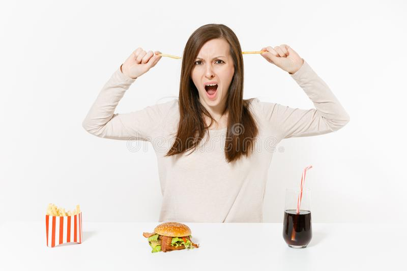 Dissatisfied woman at table with several pieces of potatoes, french fries, burger, cola in bottle isolated on white royalty free stock images