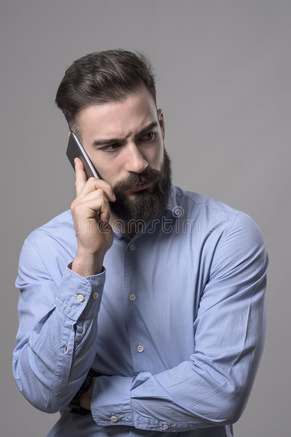 Dissatisfied young businessman talking on the phone with intense look back over shoulder royalty free stock photo