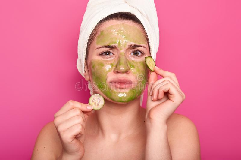 Dissatisfied young cute woman doesnt like smell from beauty mask, discontent with effect, holds two slices of cucmber, removes royalty free stock image