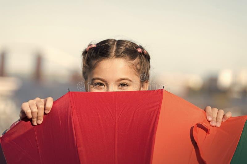 Dissimulation des probl?mes Scintillement positif et lumineux fant Position mignonne d'enfant de fille avec le parapluie color? E images stock