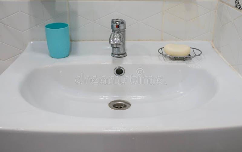 Dissipador cerâmico branco no banheiro com vidro plástico para a escova e sabão para a limpeza da mão imagem de stock royalty free