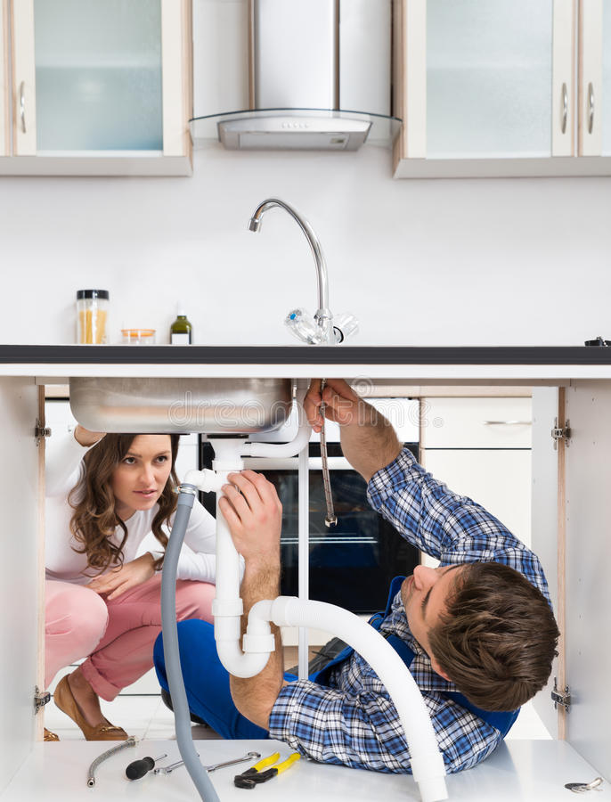 Dissipador da fixação do trabalhador em Front Of Woman In Kitchen fotografia de stock royalty free