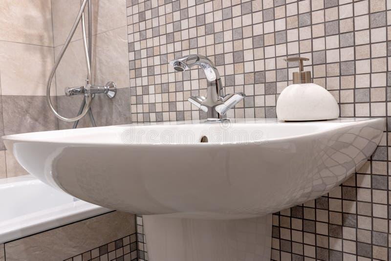 Dissipador limpo branco do banheiro com torneira brilhante e o prato de sabão de pedra fotos de stock