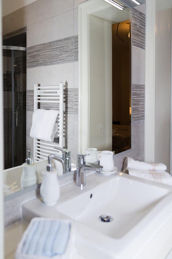 Dissipador, torneira, toalhas e grupo do banheiro DES interior do banheiro moderno foto de stock