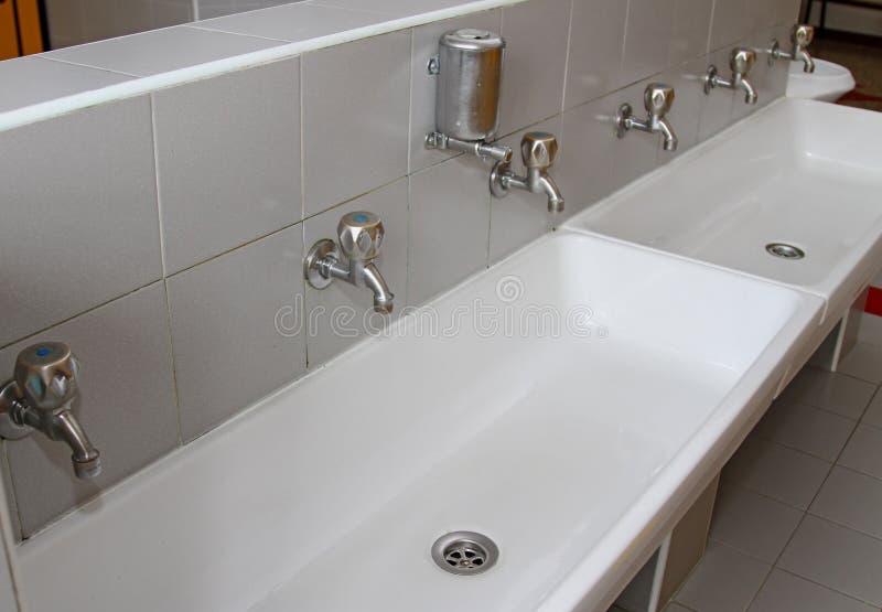 Dissipadores e bacias com as torneiras nos toaletes de um berçário imagens de stock royalty free