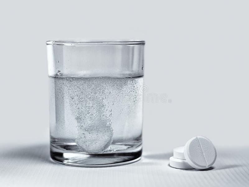 Dissolving effervescent tablets. Closeup of effervescent tablets dissolving in a glass of water royalty free stock photo