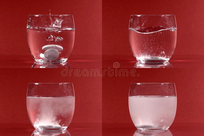 Dissolving effervescent tablets. Four images of dissolving effervescent white tablets in a glass of water on a red background royalty free stock images