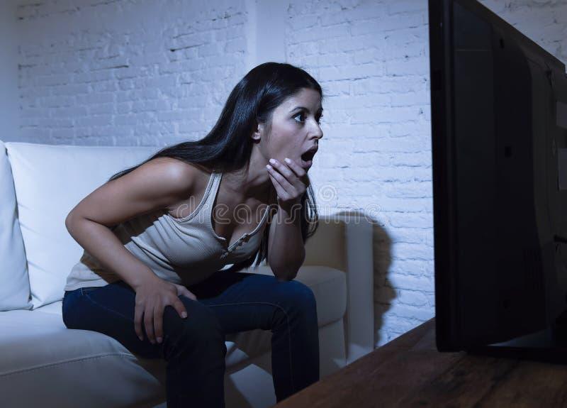 Distância próxima de observação home da televisão da mulher latino entusiasmado no conceito do apego da tevê fotografia de stock