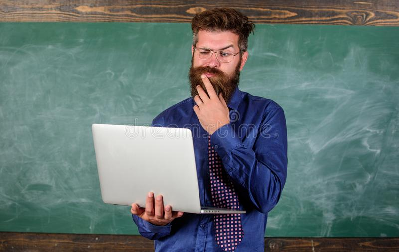 Distance education concept. Teacher bearded man with modern laptop surfing internet chalkboard background. Surfing. Internet. Hipster teacher wear eyeglasses royalty free stock images