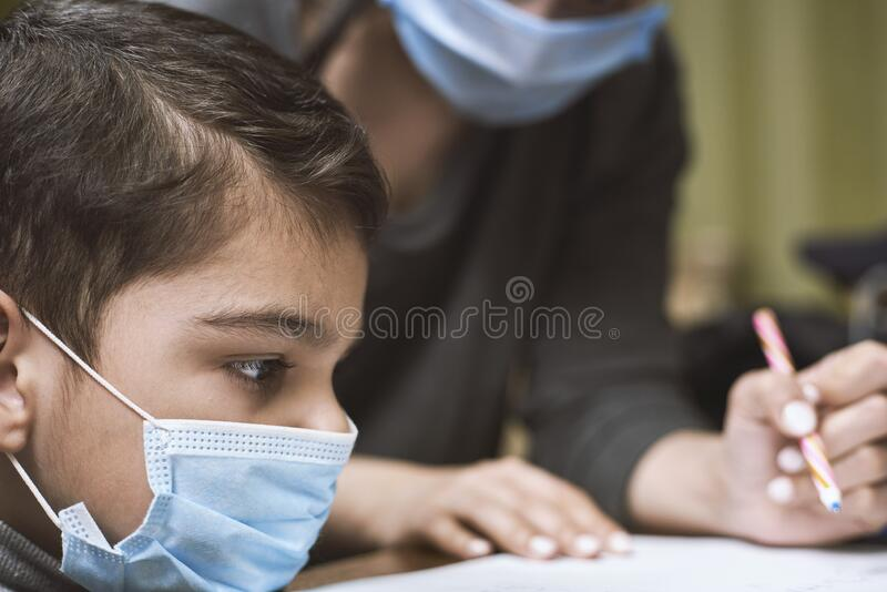 Distance education. Mother helps a pre-school kid to do lessons. Distance education. Mother helps pre-school kid to do lessons. Education at quarantine time royalty free stock image