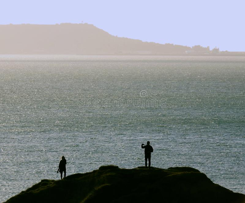 Silhouette of a couple on a cliff top with man taking a selfie stock photo