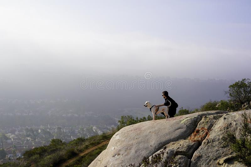 Distance shot of a male with his companion dog squatting on a rocky hill royalty free stock photo