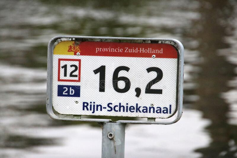 Distance sign along the river side of the Rijn-Schiekanaal canal in Leidschendam in the Netherlands royalty free stock photos