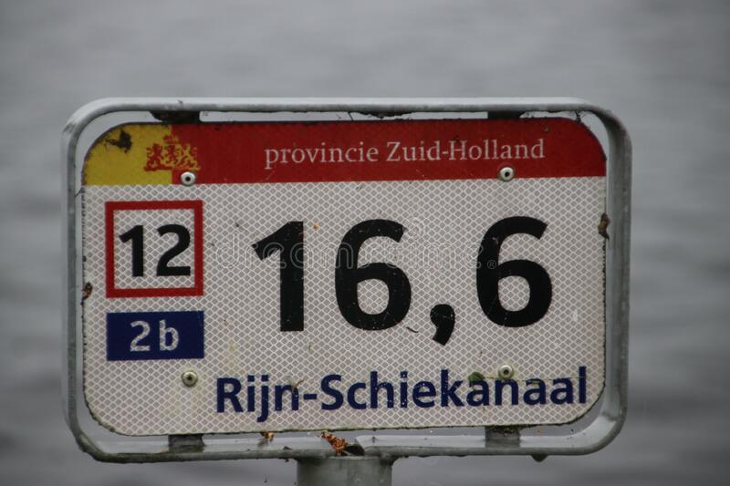 Distance sign along the river side of the Rijn-Schiekanaal canal in Leidschendam in the Netherlands stock photo