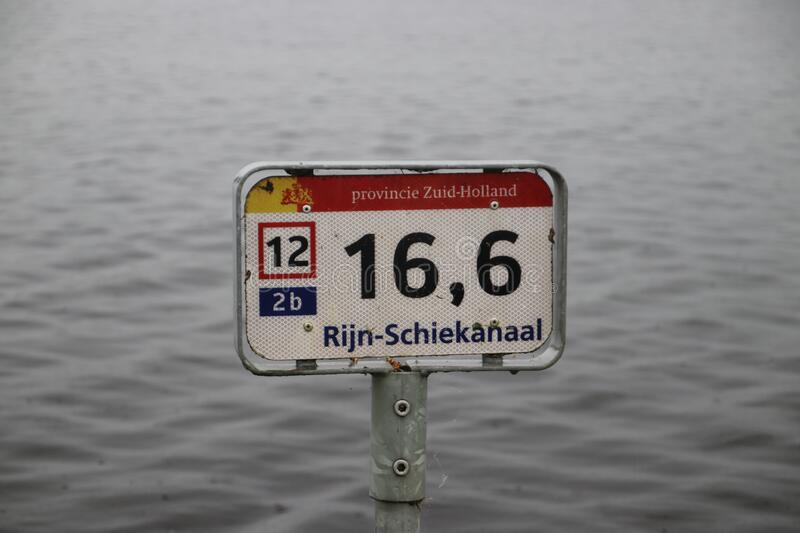 Distance sign along the river side of the Rijn-Schiekanaal canal in Leidschendam in the Netherlands stock images