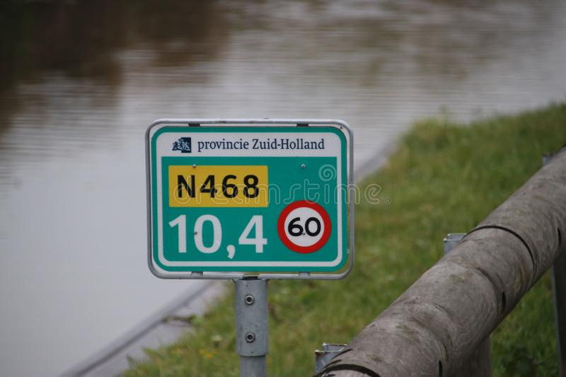 Distance sign on provincial road N468 at Schipluiden in the Netherlands with speed limit 60 kilometers. stock photo