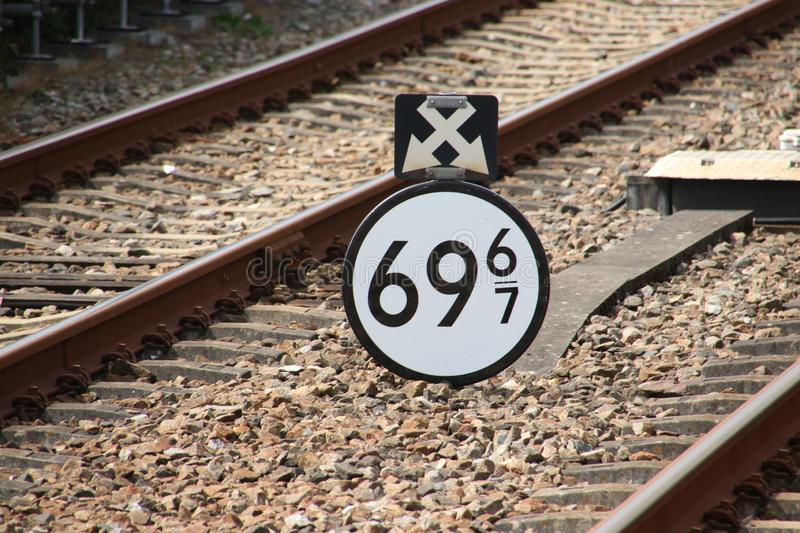 Distance sign between the railroad track between Amersfoort and Zwolle at station `t harde during autumn stock image
