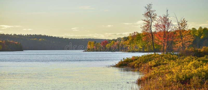 In the distance, two people in a boat L'après-midi de fin d'été, le soleil brille la lumière d'or sur un lac photo stock