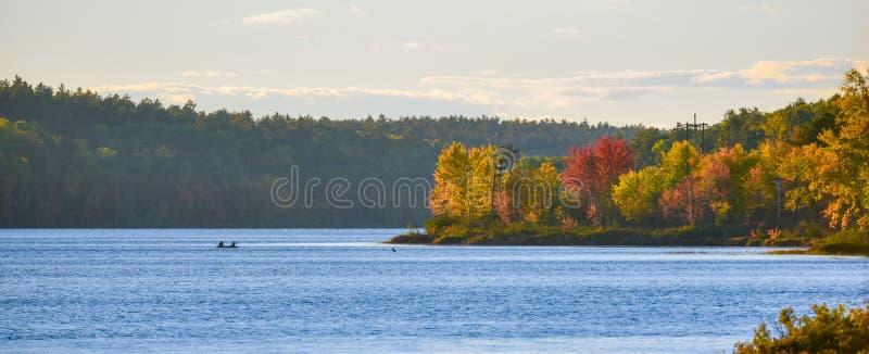 In the distance, two people in a boat L'après-midi de fin d'été, le soleil brille la lumière d'or sur un lac photos libres de droits