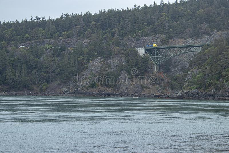 Distant forested seaside cliffs with a bridge crossing the gap royalty free stock image