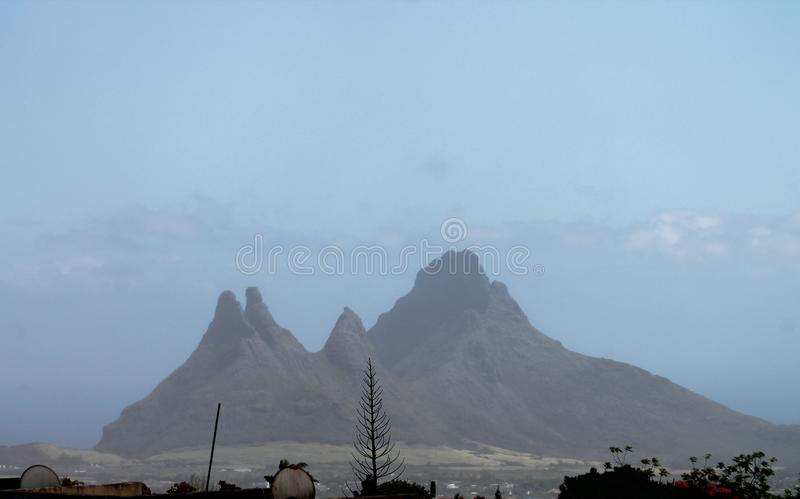 Hazy mountain peaks in Mauritius. A distant, hazy view of the Trois Mamelles mountain, situated in Mauritius stock image