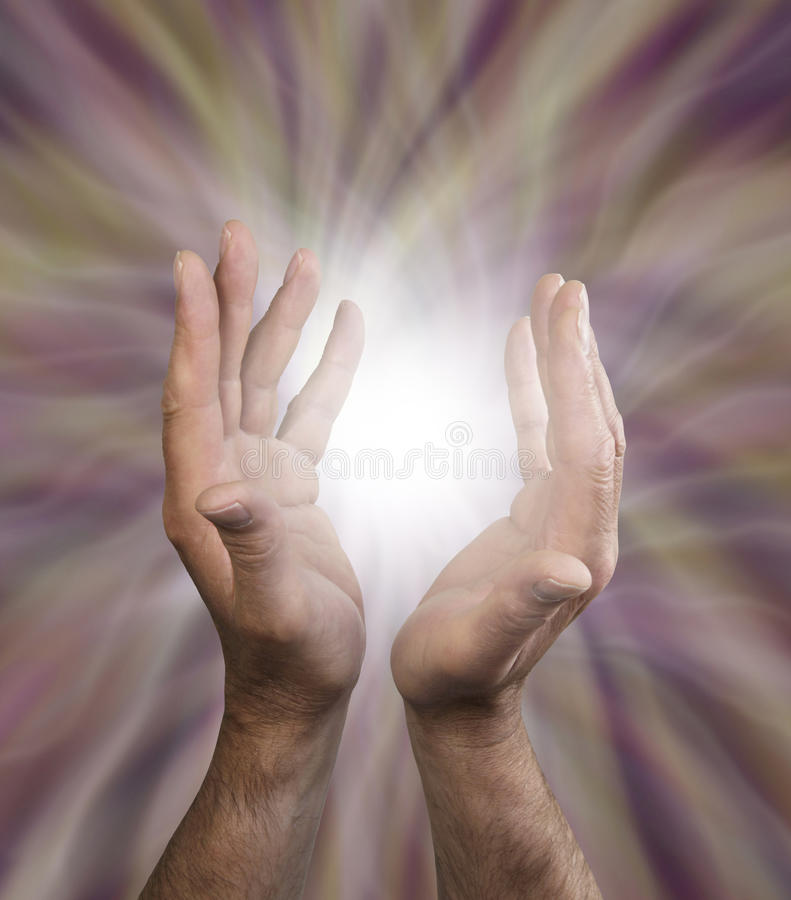 Distant healing. Male healing hands outstretched with energy field and ball of light between hands royalty free stock photo