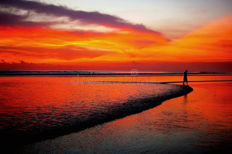 Distant man walking on beach at sunset. Silhouette of man in distance walking on beach at sunset, Double Six beach, Seminyak, Bali royalty free stock photo