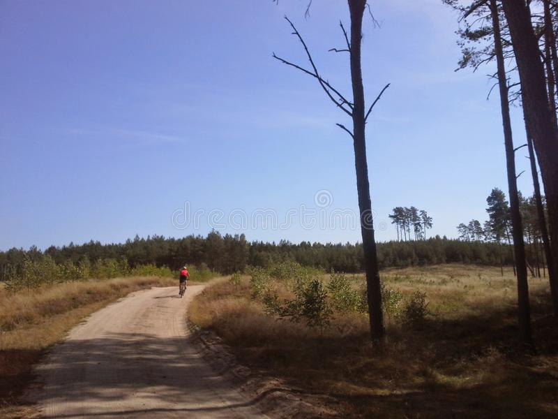 Distant mountain bike cyclist on dirt path royalty free stock photography