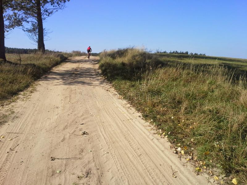 Distant MTB cyclist on dirt path royalty free stock images