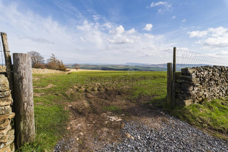 Distant Pendle. Looking through a gateway on Merrybent hill towards a distant Pendle Hill in Lancashire, England stock photos