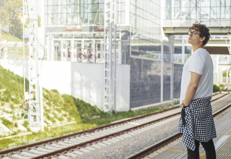 Distant plan of young attractive man waiting for train in metro station. Man is on focus and foreground, metro station is on background royalty free stock image