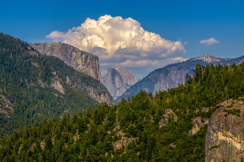 Distant view of Half-Dome in Yosemite National Park. Clouds above the stunning half-dome mountain in Yosemite National Park on a lovely summer day stock photography
