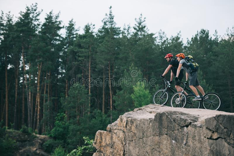 distant view of male extreme cyclists in protective helmets riding on mountain bicycles on rocky cliff royalty free stock images