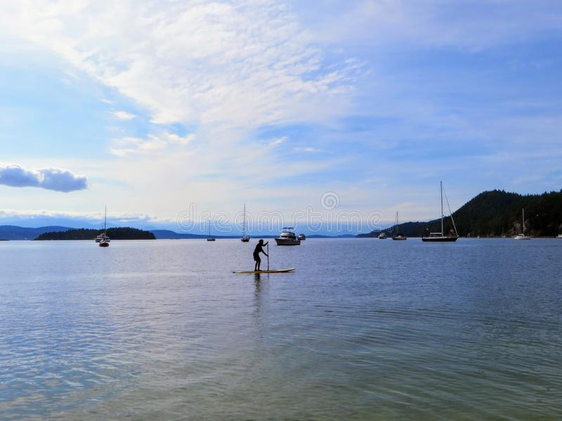 A distant view of a person paddle boarding alone on the open ocean off of galiano island, British Columbia, Canada. royalty free stock photos