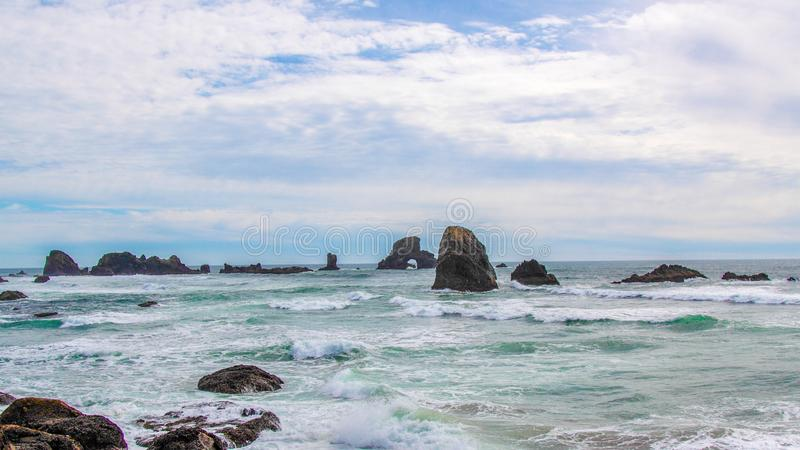 Distant view of a stone arch at Sea Lion Rock, Oregon stock photography