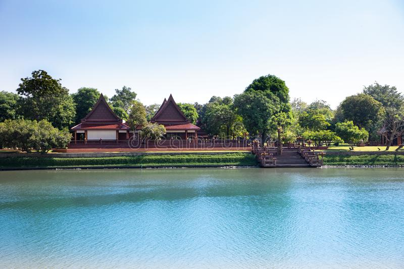 Distant view of a typical Thailand landscape with a blue river and temple roofs and green trees in the background royalty free stock photography