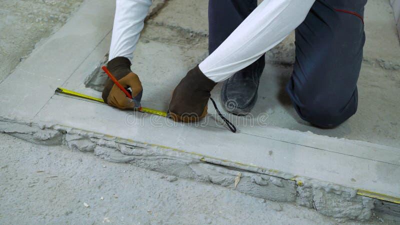 Distanze di misure del costruttore con nastro adesivo e la matita di misurazione al cantiere fotografia stock