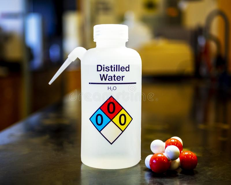 Distilled water bottle. Used in laboratories with name, safety code and molecular models of water showing red oxygen and white hydrogen stock photography
