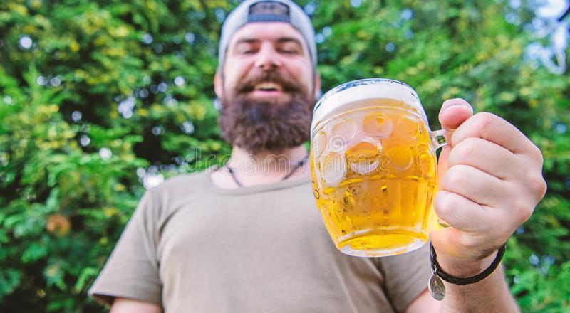 Distinct beer culture. Hipster brutal bearded man hold mug cold fresh beer. Man relaxing enjoying beer in summer. Alcohol drink and bar. Craft beer is young stock photography