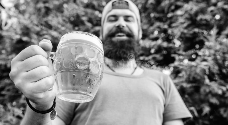 Distinct beer culture. Hipster brutal bearded man hold mug cold fresh beer. Man relaxing enjoying beer in summer. Alcohol drink and bar. Craft beer is young stock image
