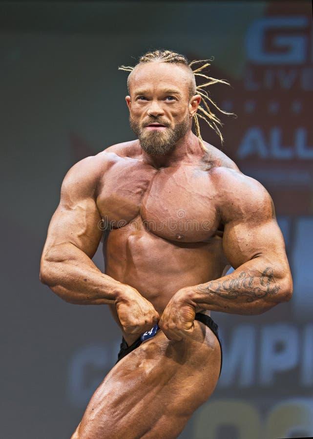 Distintively Coiffed Aussie Bodybuilder Grabs Attention bij de Wedstrijd van Toronto stock fotografie