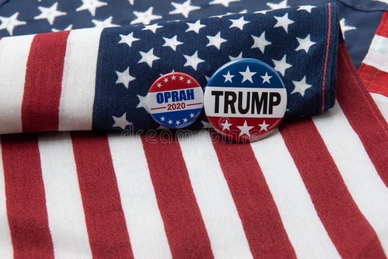 Distintivo presidenziale di Oprah 2020 e distintivo 2020 di Trump contro la bandiera degli Stati Uniti immagini stock libere da diritti