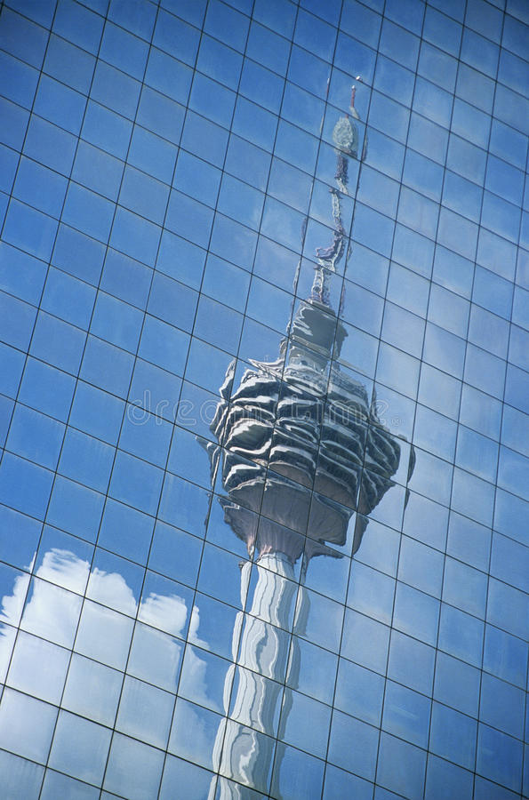 Distorted reflection of Kuala Lumpur Tower in building wall full frame stock photo