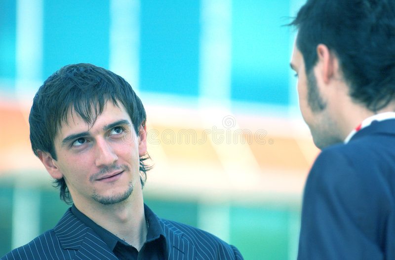 Distracted Businessman. Two male coworkers in a discussion, one is distracted and looking away. Blue tinted royalty free stock photography
