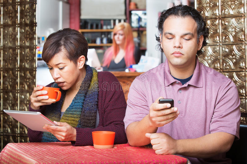 Distracted Couple Using Devices. Young distracted African American couple using digital devices in cafe stock image