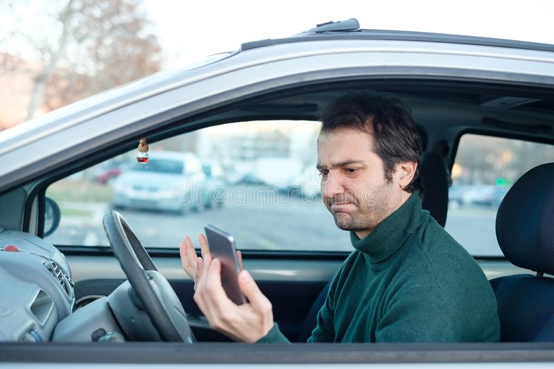 Distracted and dangerous driving smartphone.Traffic violation. Man driver talking on a mobile phone in the car. Distracted and dangerous driving stock photo
