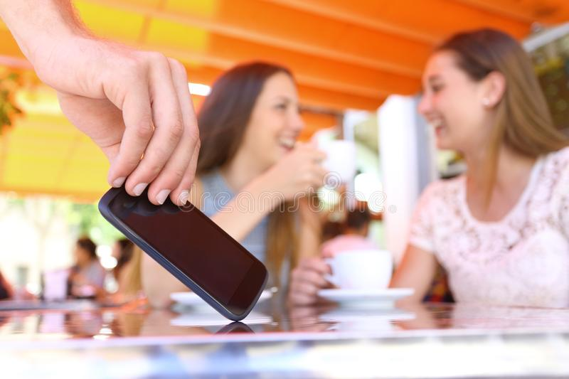 Distracted friends talking in a bar and thief stealing phone royalty free stock image