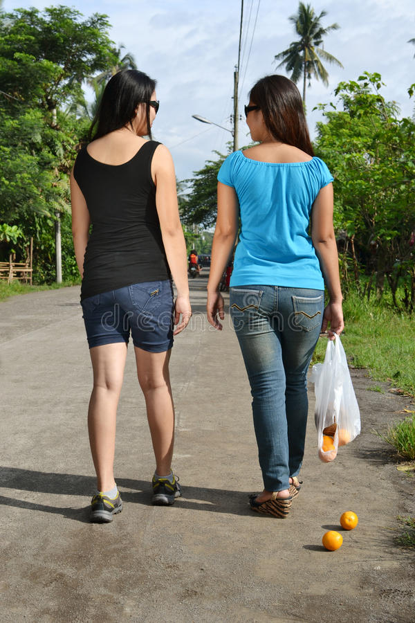 Distracted friends. Two distracted friends while the shopping bag is broken stock photography