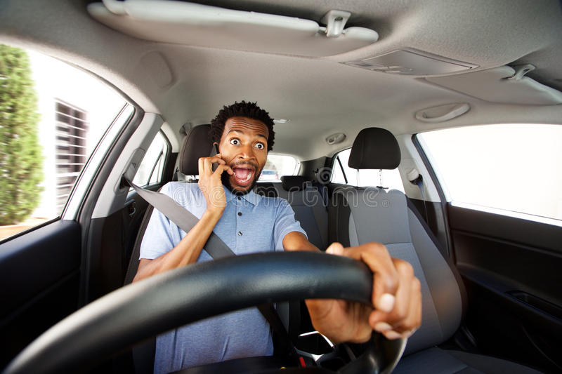 Distracted man driving in car talking on smart phone. Close up portrait of distracted man driving in car talking on smart phone stock photography
